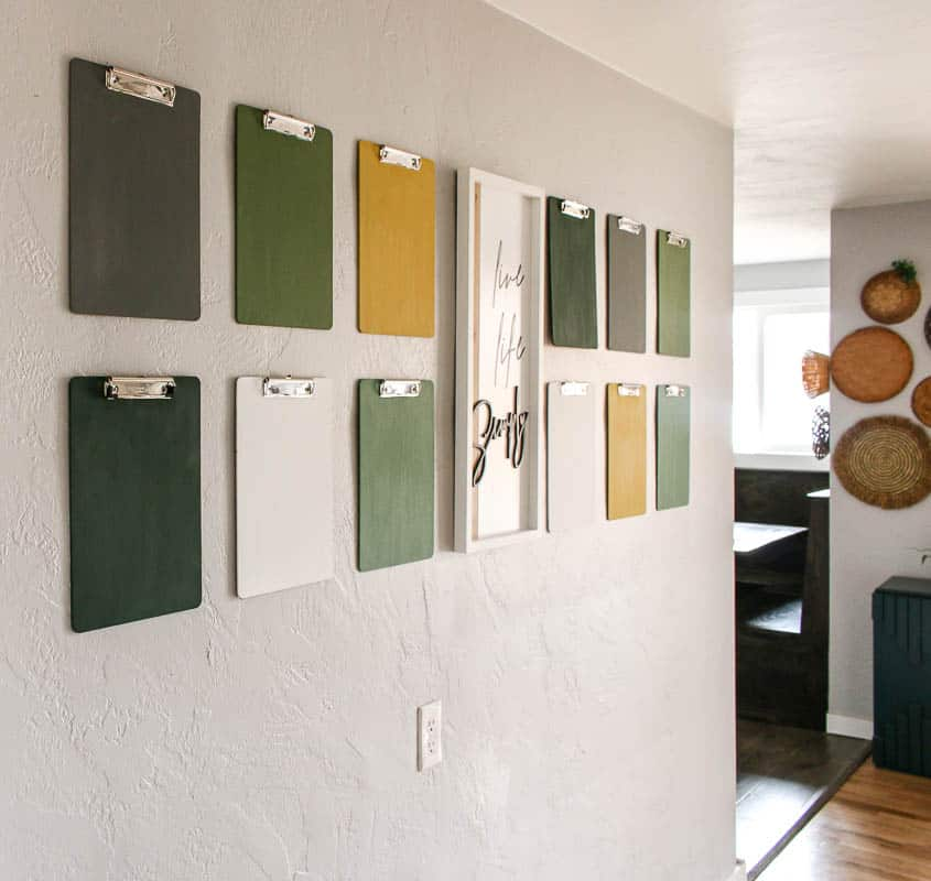 shows 12 gray, green, white, and yellow clipboards on a gray wall with a white live life simply frame in between the clipboards