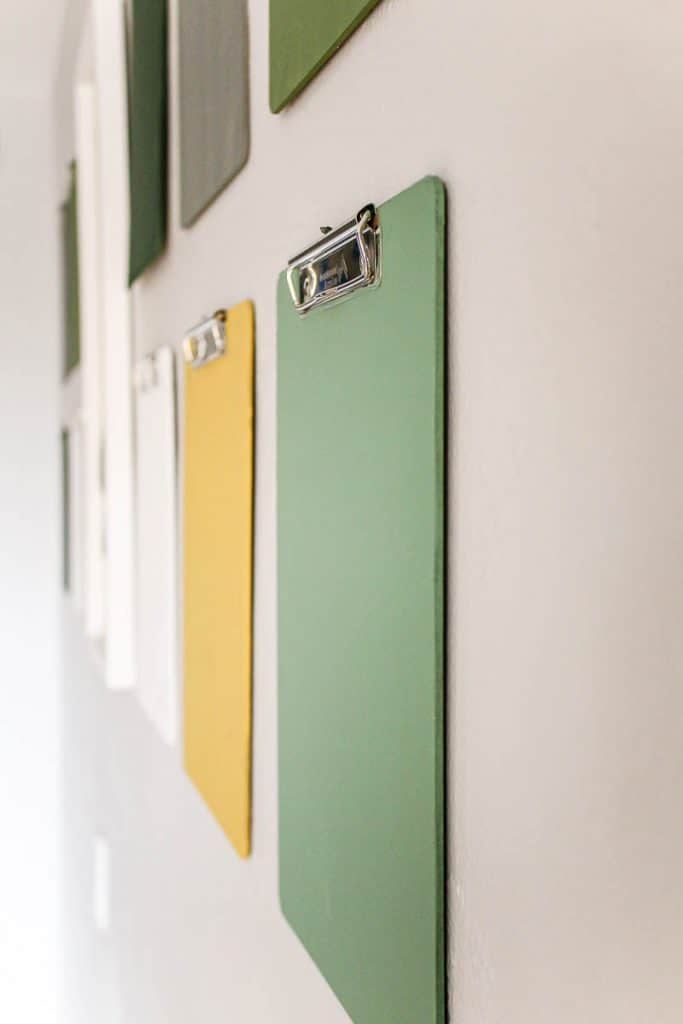 shows a side angle of the 12 colorful clipboards hanging on a gray wall with a white frame in the middle of the clipboards