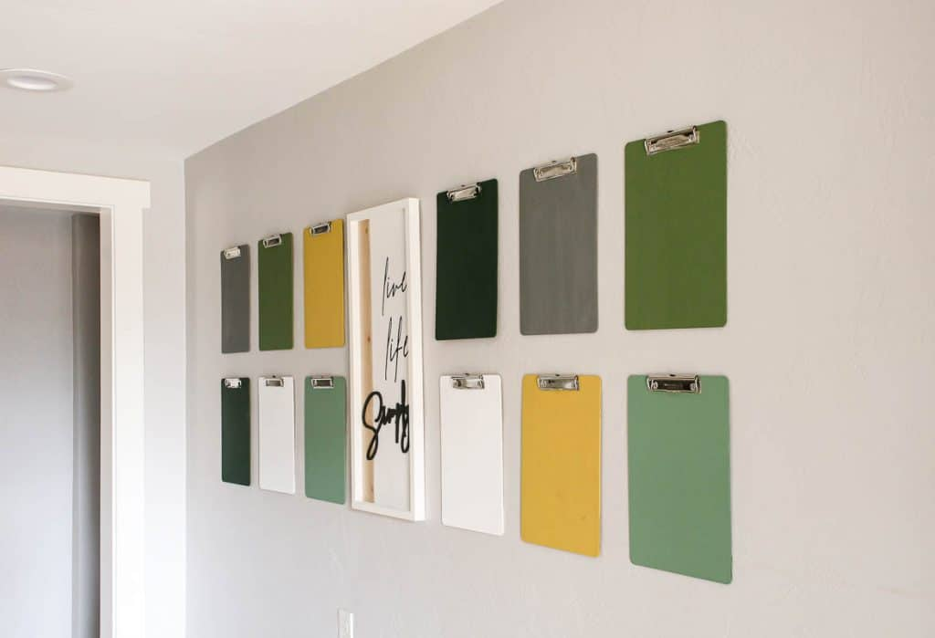 shows a side angle of 12 green, gray and yellow clipboards hanging on a gray wall with a live life simply frame hanging in between them