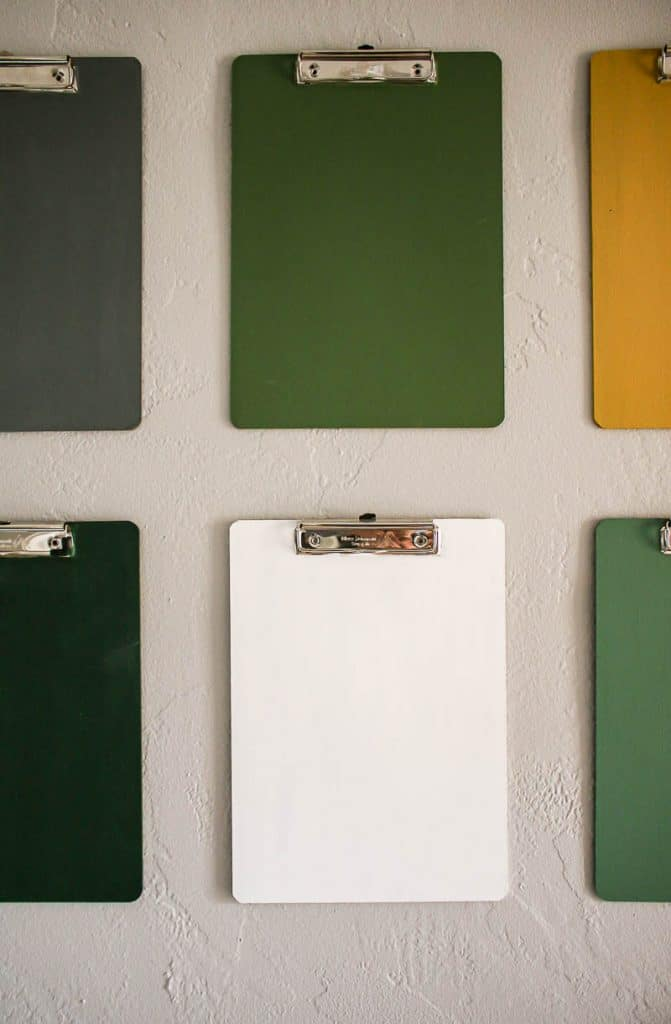 shows an up close picture of the colorful clipboards on a gray wall