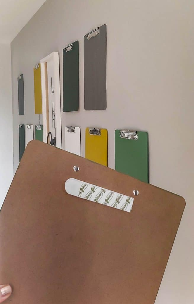 shows numerous colorful clipboards hanging on a gray wall and one in front with a command strip on the back