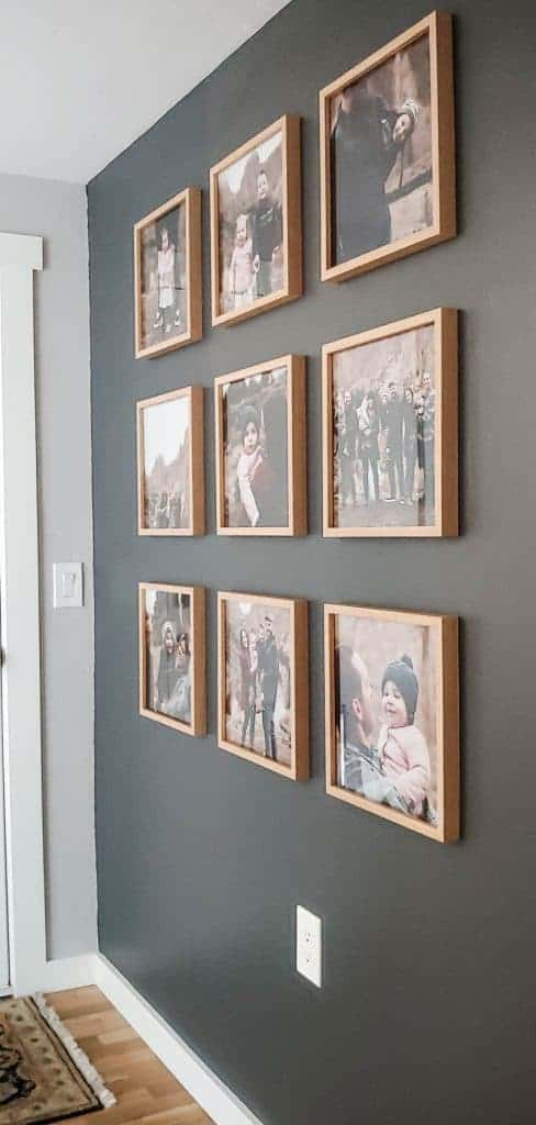 shows a side angle view of 9 family photos on a dark gray wall in light wood frames