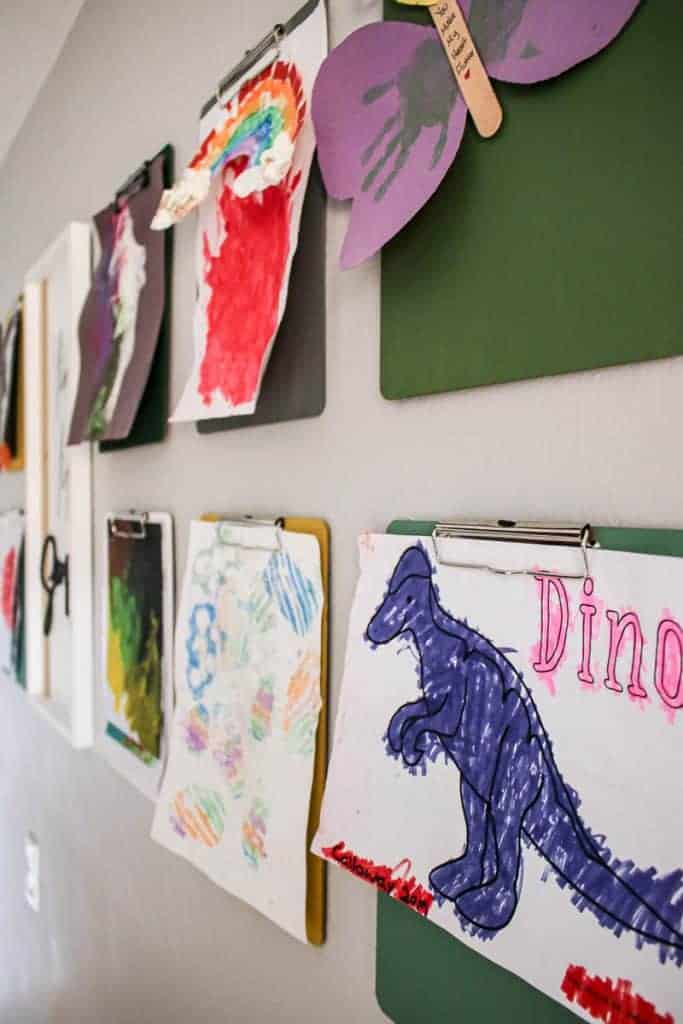 shows the colorful clipboards with kids paintings and drawing hanging from them