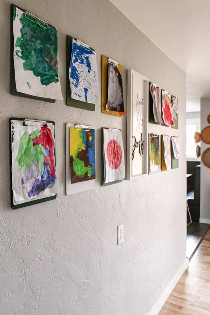 shows a side angle of 12 clipboards with kid's artwork hanging from them with a white live life simply frame hanging in between them.