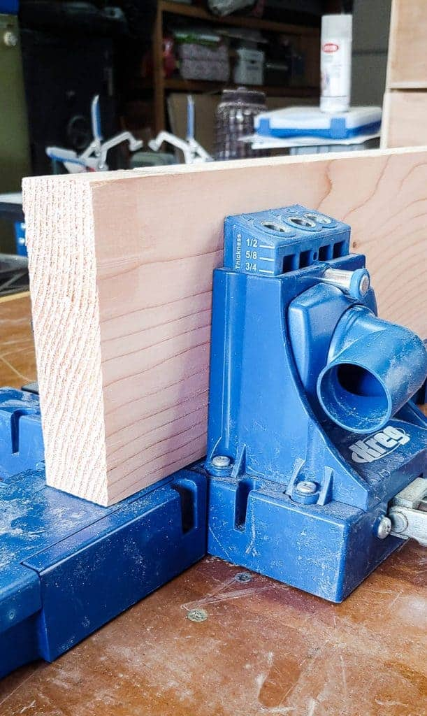 Shows a piece of wood in a Kreg pocket hole jig