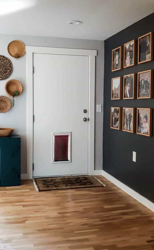 shows a modern boho hallway with a white door with wood floors. On the left side has a wicker basket wall with a green cabinet and on the left shows a gray wall with 9 family photos in a grid pattern