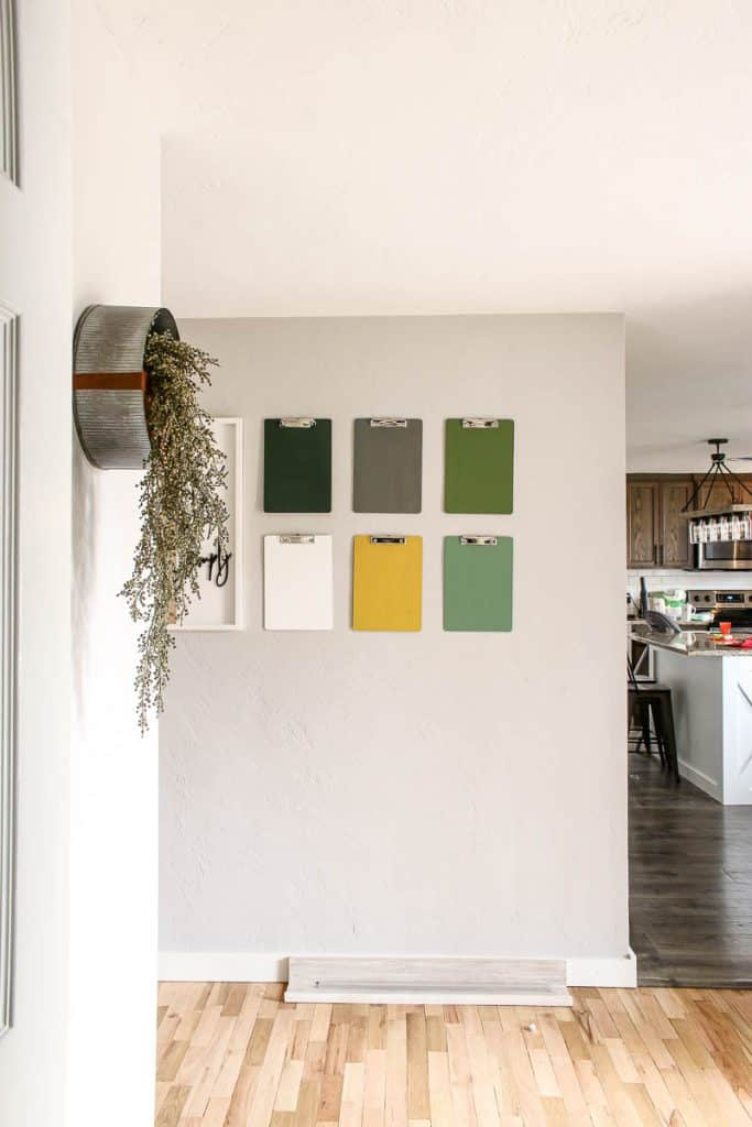 6 colorful clip boards and a white frame hanging on it with a metal planter on the side with a kitchen in the background