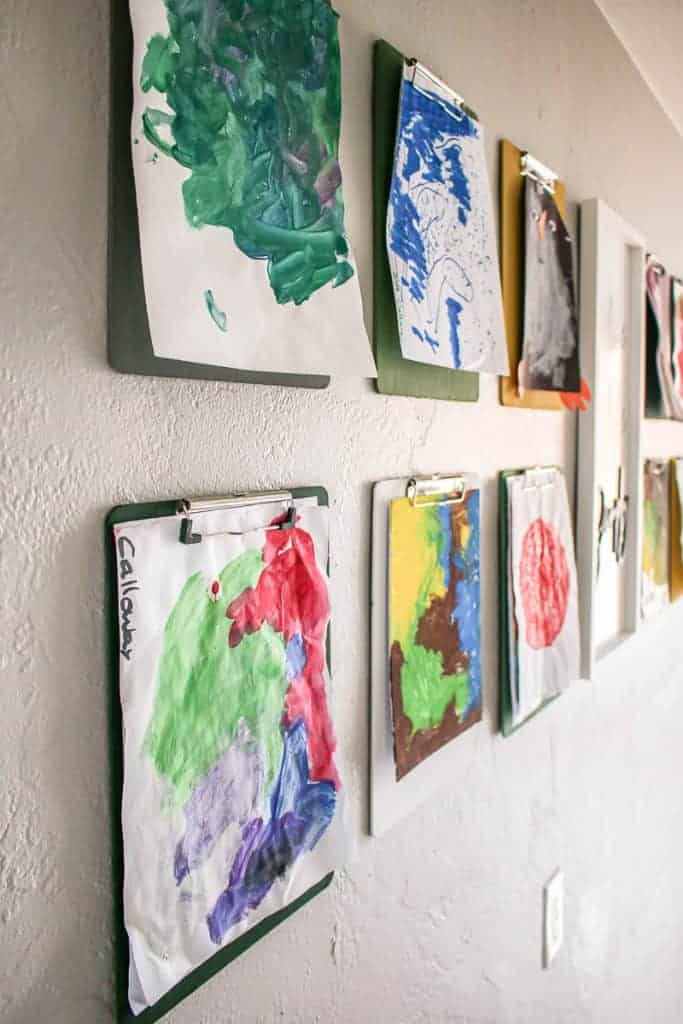 shows an up close picture of a kid's paintings hanging from clipboards