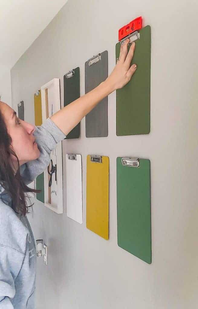 shows a woman using a level to hang a clipboard evenly on a wall with other colorful clipboards on a gray wall