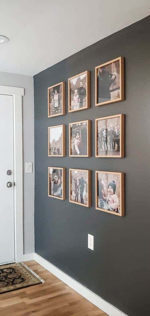 shows 9 photos in a grid pattern with wood frames on a dark gray wall and wood floors