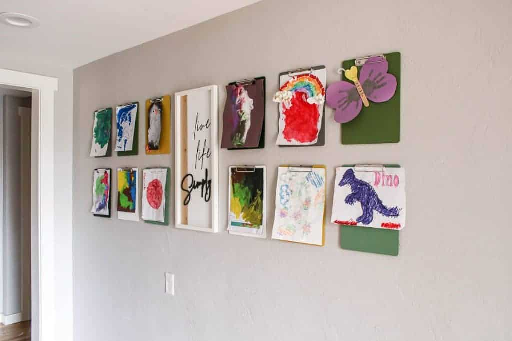 shows 12 clipboards with kid's paintings hanging from them on a gray wall with a live life simply frame hanging in between them