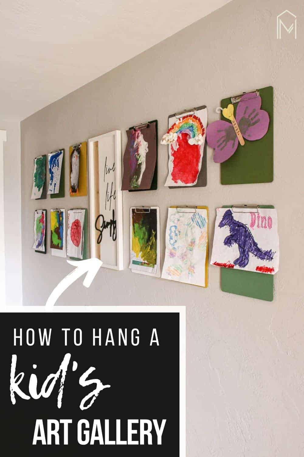 shows 12 clipboards with kid's paintings hanging from them on a gray wall with a live life simply frame hanging in between them with overlay text that says how to hang a kid's art gallery
