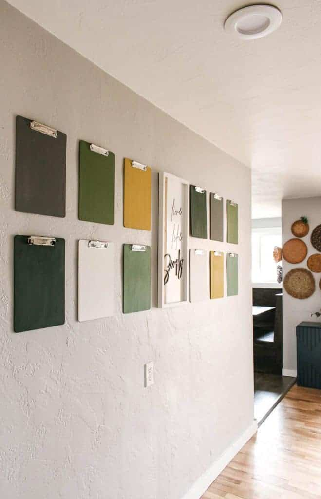 shows 12 colorful clipboards hanging on a gray wall with a white live life simply frame hanging in between the clipboards