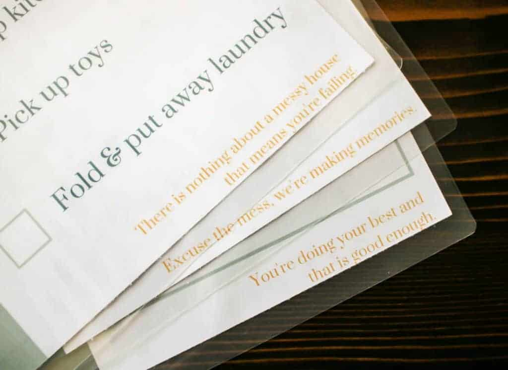 shows laminated cleaning schedules with encouraging quotes on a dark wood table