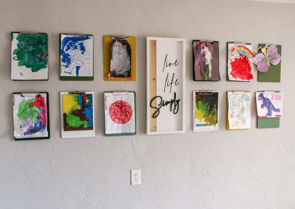 shows a face on view of 12 colorful clip boards with kid's artwork hanging from them on a gray wall with a white live life simply frame hanging in between