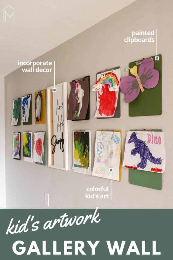 shows a side angle of 12 clipboards with kid's artwork hanging from them on a gray wall with a white live life simply frame hanging in between them. With overlay texts that says Kid's Artwork Gallery Wall