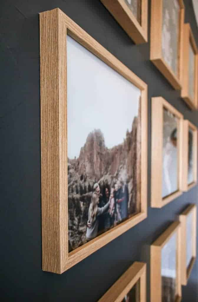shows a side angle of family photos on a gray wall in light wood square frames