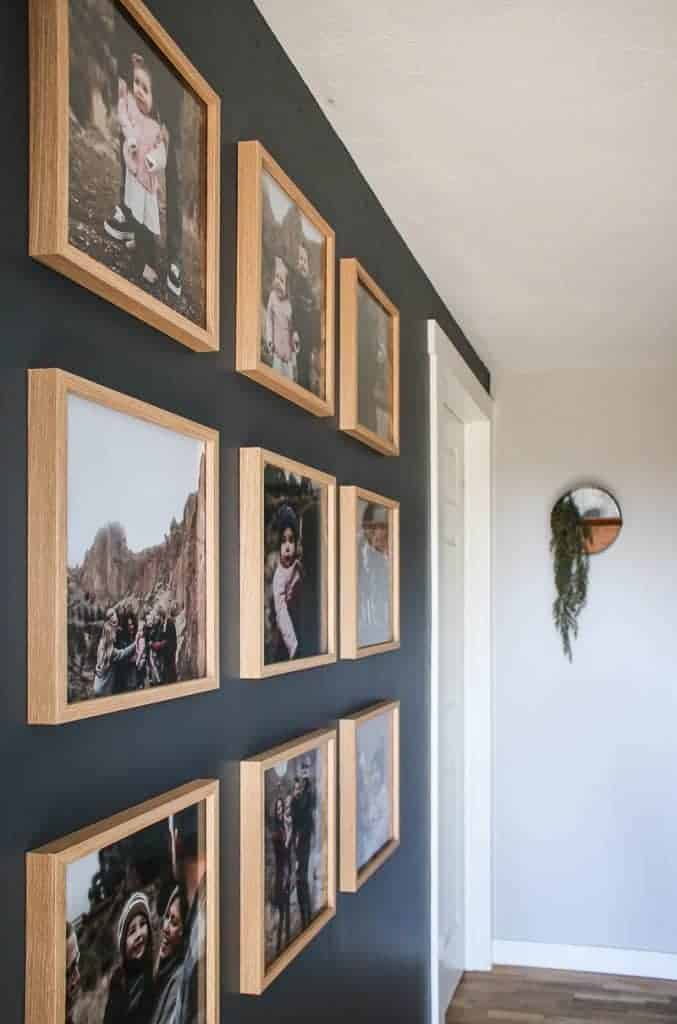 shows a 9 different family photos in wood frames on a gray wall in a grid pattern