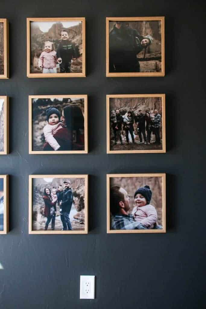 shows a third of the family photos hung on a gray wall in a grid pattern