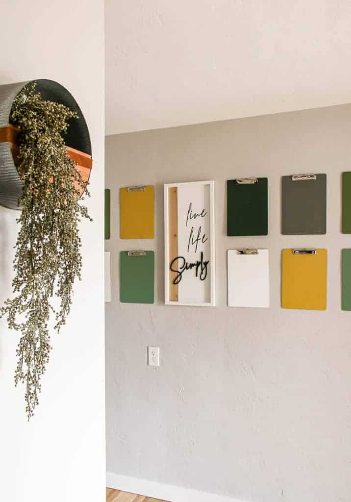 shows numerous colorful clipboards hanging on a gray wall with a live life simply frame hanging in between with a metal wall planter hanging in the left