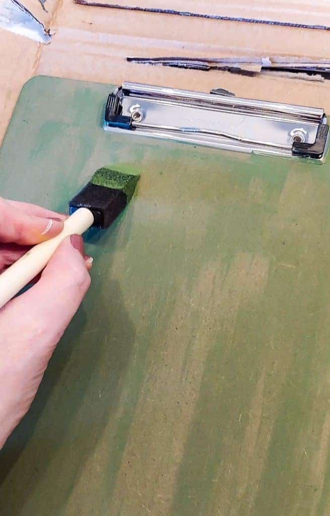 Shows a hand painting a clipboard on cardboard with green paint