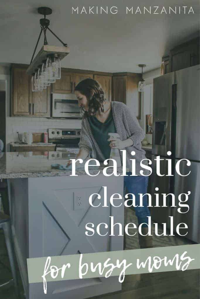 Shows a woman cleaning her modern farmhouse kitchen with overlay text that says realistic cleaning schedule for busy moms
