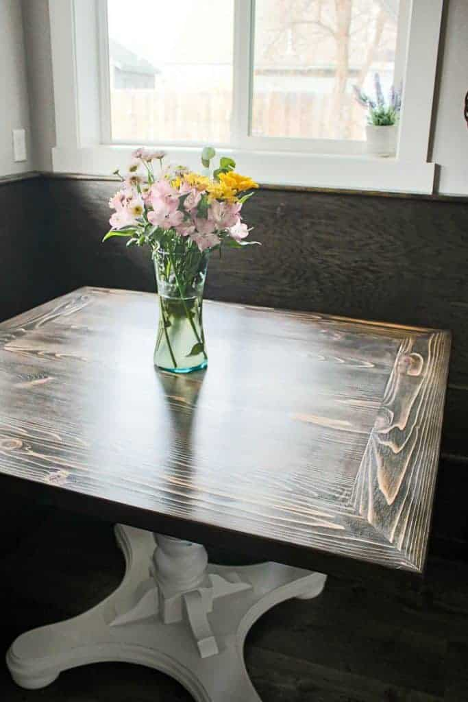Shows a dark wood farmhouse breakfast nook with a square wood tabletop and white base with a vase of flowers