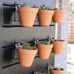 shows a side view of 9 vertical garden pots with succulents hanging on a black wood wall mounted on the side of a gray brick house with overlay texts that says DIY plant wall