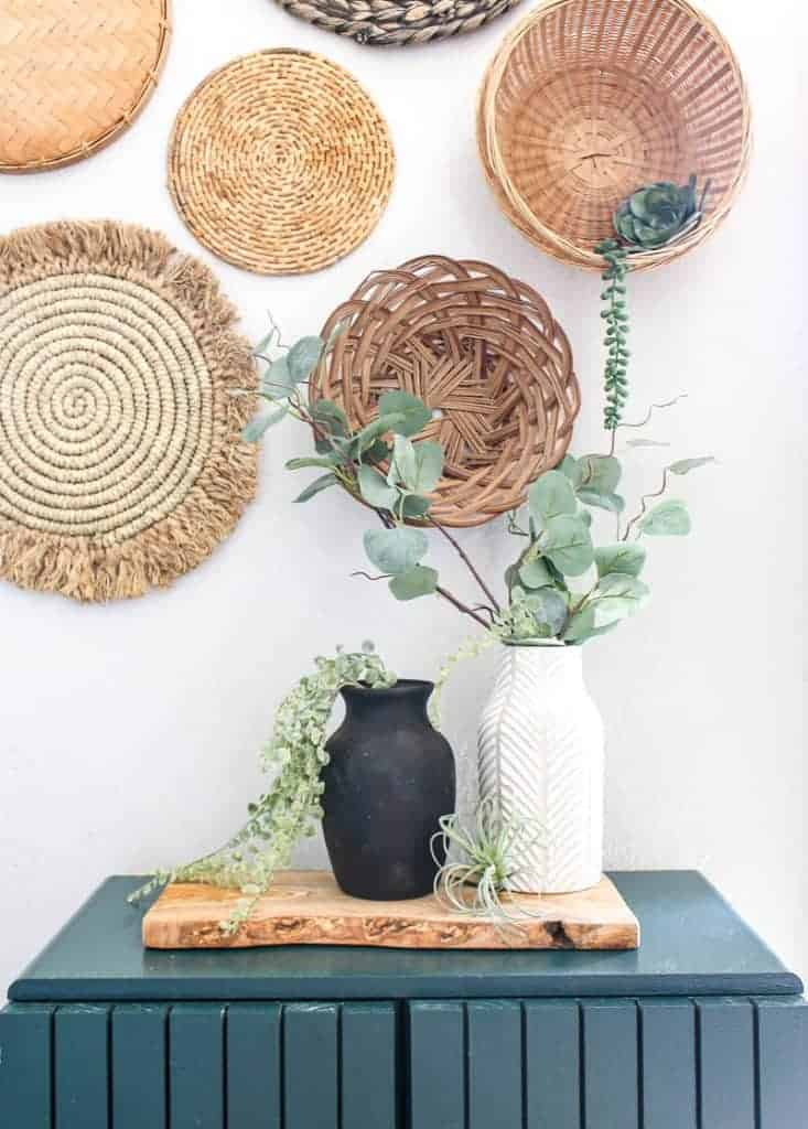 shows a black vintage vase and white vase with greenery sitting on a wood plank in a teal cabinet with a wicker basket wall in the background