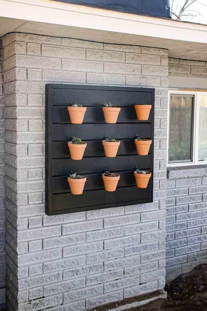 shows 9 terracotta pots hanging for a black wood wall on a side of a brick house