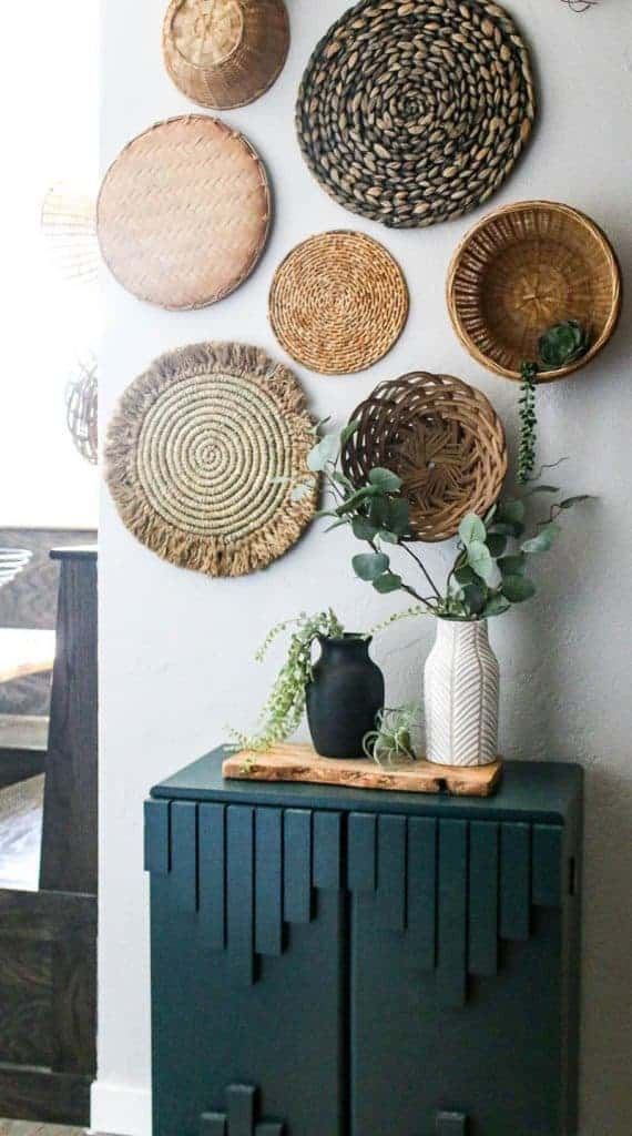 shows a black and white vintage looking vases siting on a wood plank and teal cabinet with greenery hanging out of them with a wicker basket wall in the background