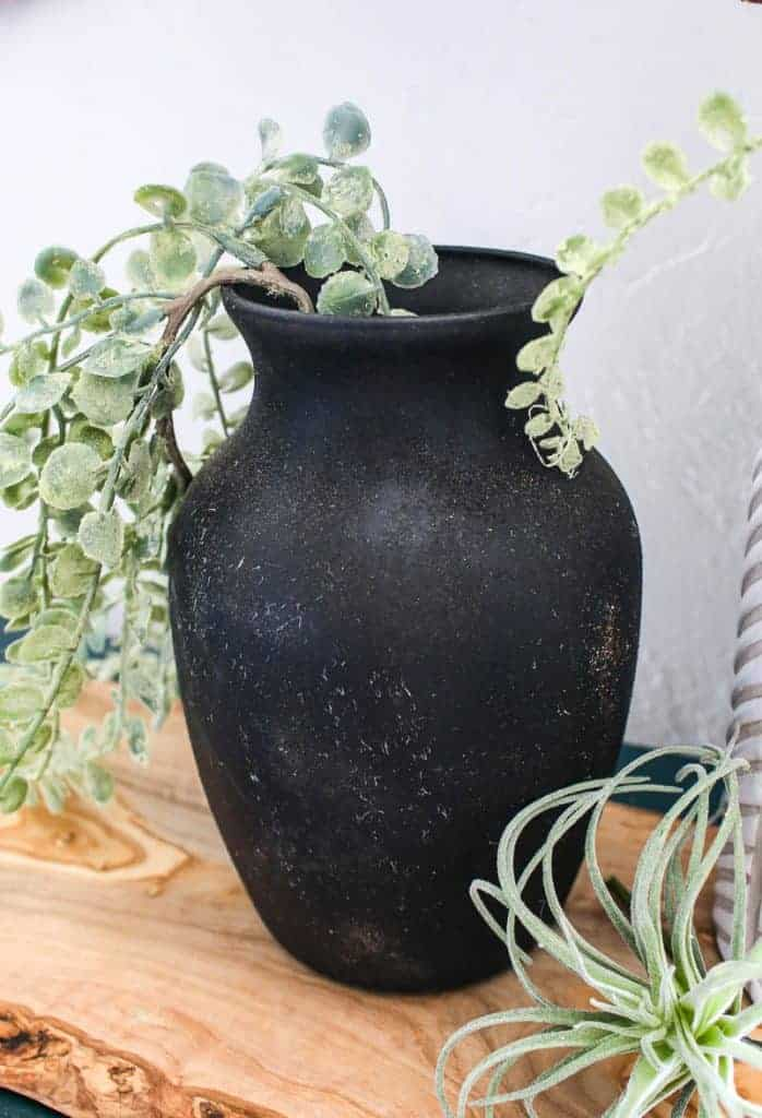 shows a vintage black vase with greenery sitting on a wood plank