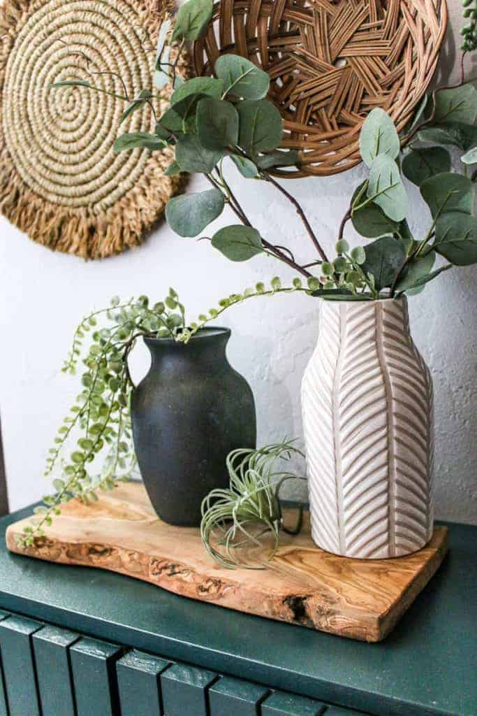 shows a black and white vase sitting on a green cabinet and wood plank with greenery in them