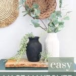 shows a black and white vintage looking vases siting on a wood plank and teal cabinet with greenery hanging out of them with a wicker basket wall in the background with overlay text that says easy vase makeover (spray paint and dirt)