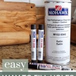 shows Mohawk products such as Fil-Stik, brush tip markers and spray can on a granite counter with text at bottom that says easy way to fill in holes in stained wood