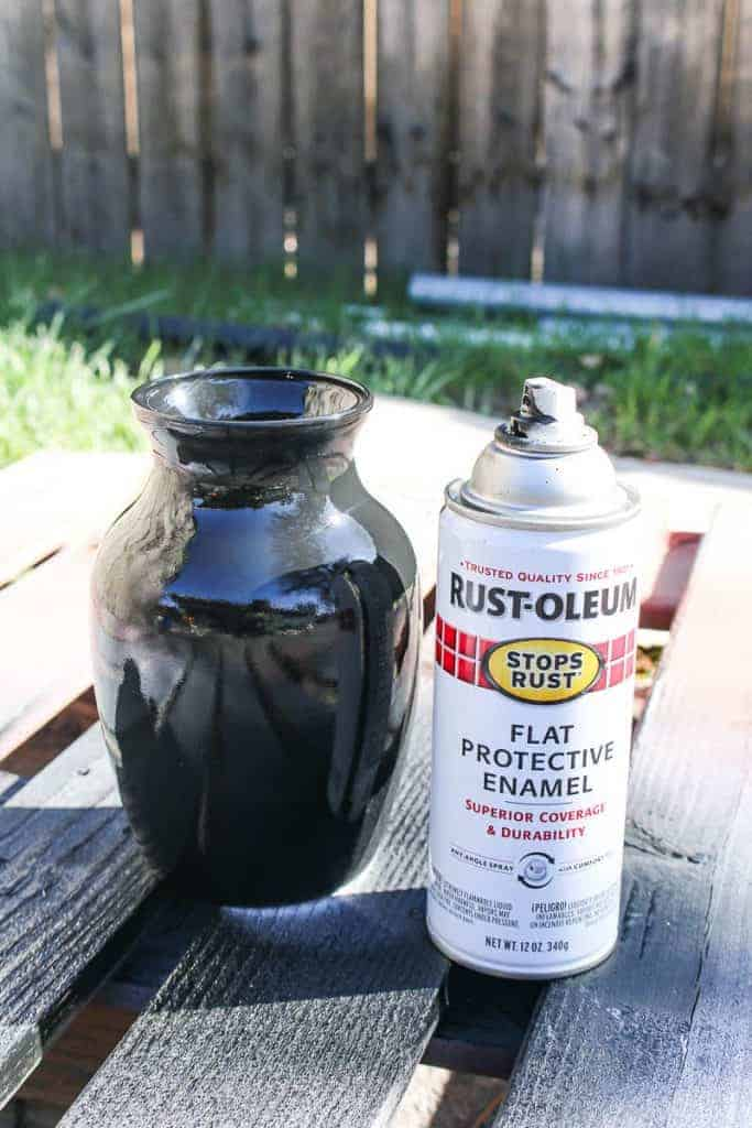 shows the glass vase painted black with rust-oleum spray paint sitting ona wood pallet outside