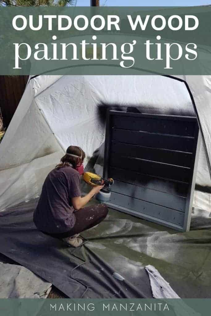 Woman using a paint sprayer to spray black exterior paint on wooden structure in a spray shelter tent with text overlay that says outdoor wood painting tips