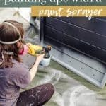 Woman holding Wagner Flexio 3000 paint sprayer and applying black paint to wood with text overlay that says outdoor wood painting tips with a paint sprayer