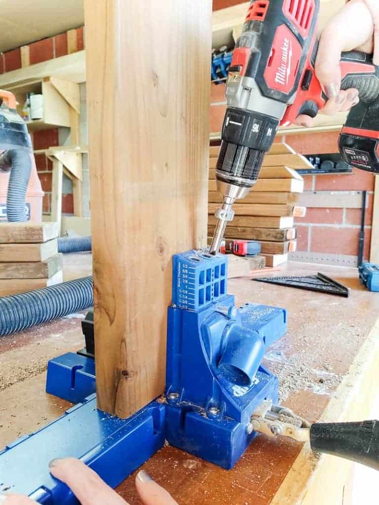 shows a drill drilling in a screw into a vertical standing wood held in place by a Kreg K5 pocket hole system