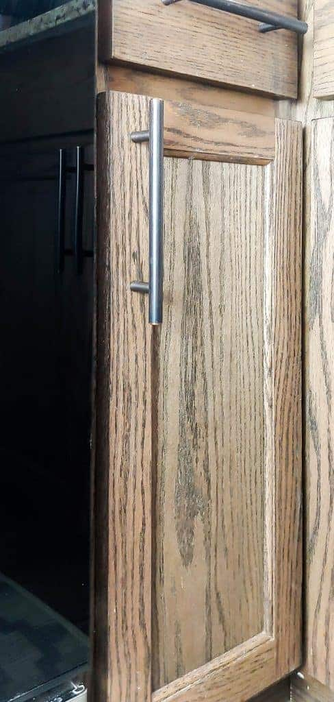 Shows the stained wood cabinet with modern oil rubbed bronze door pull