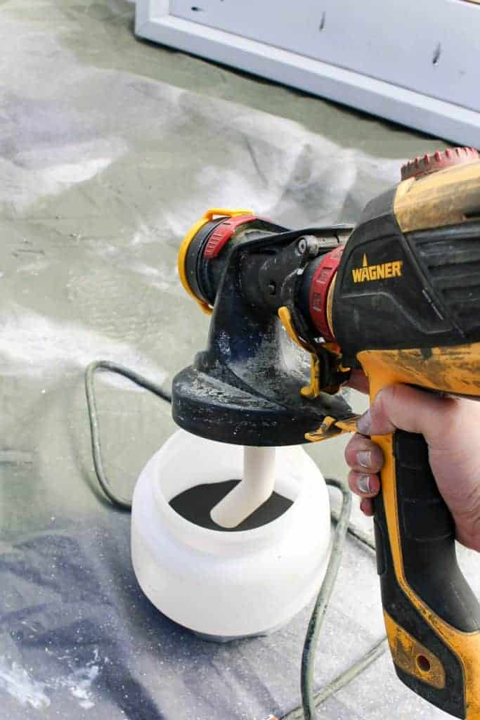 shows a Wagner paint sprayer getting ready to be used over a tarp