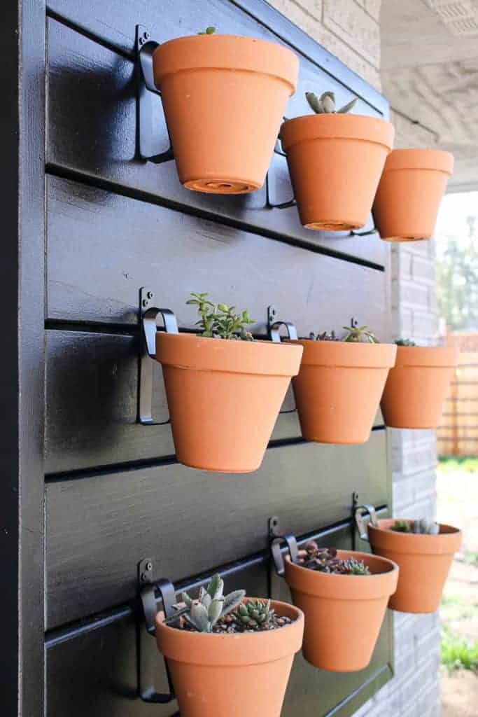 shows a side view of 9 terracotta pots with succulents hanging on a black wood wall mounted on the side of a gray brick house