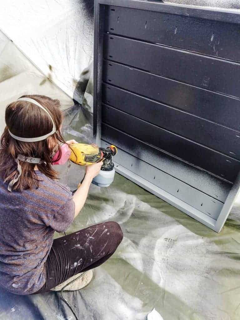 shows a woman wearing a mask using a Wagner paint sprayer in a tent to paint a wood pallet black