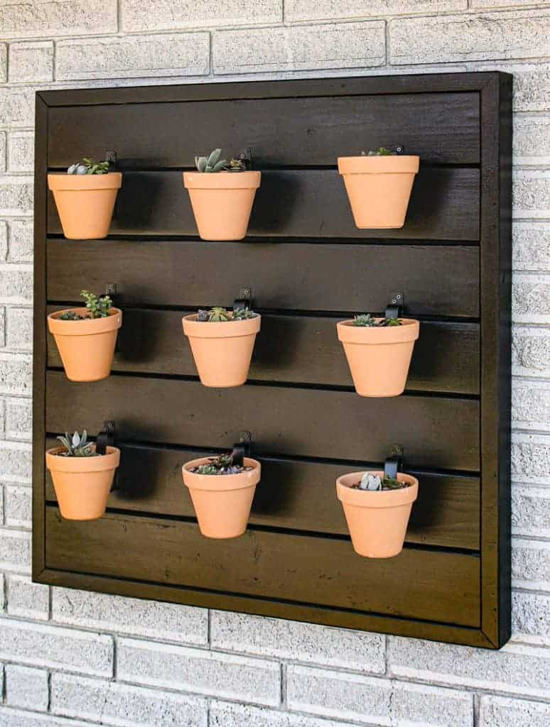 shows 9 terracotta pots with succulents hanging from a black wood wall mounted on the side of a gray brick house