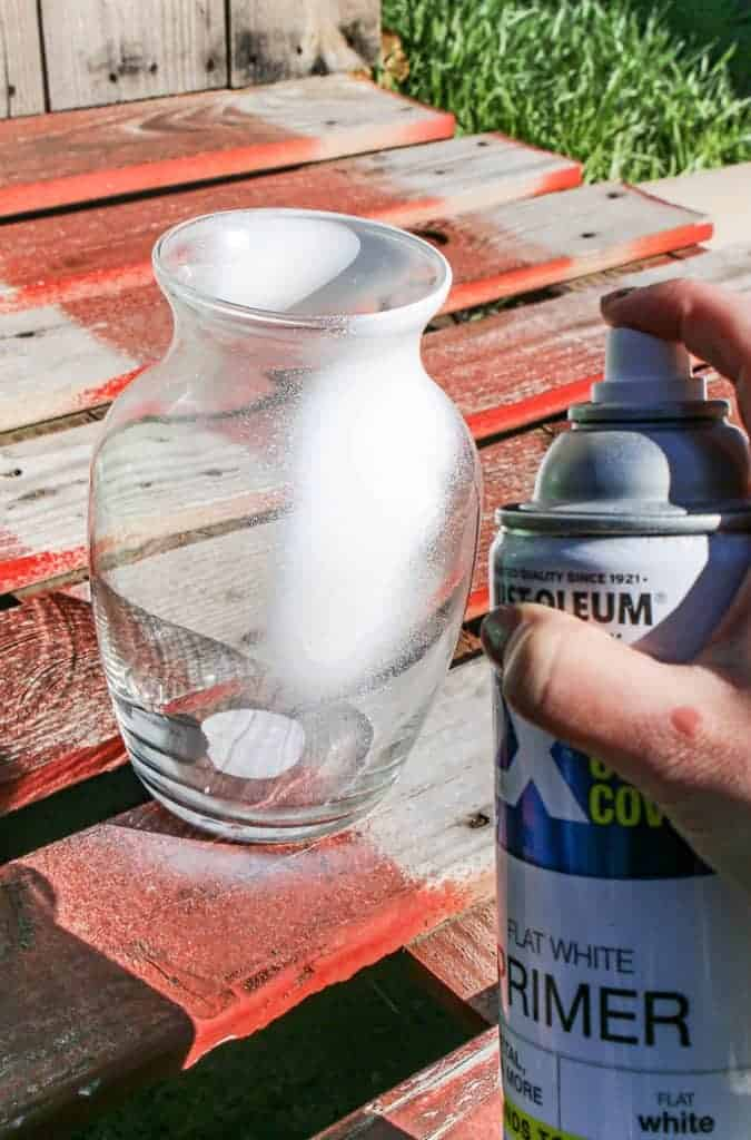 shows the clear vase being spray painted with white primer on a wood pallet outside