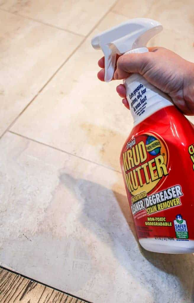 shows a hand using Krud Kutter to clean the tan tile floors