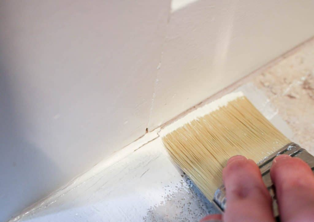 shows a paint brush painting the edge of the floor and tile