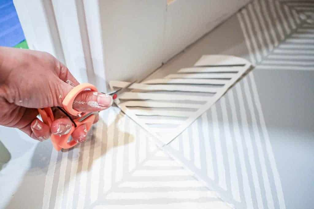 shows a pair of scissors cutting out a stencil to fit the gray floors on the edge of the room