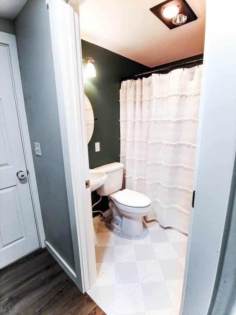 shows a boho bathroom with teal walls and gray floors with white stripes and white shower curtain, sink, and toliet