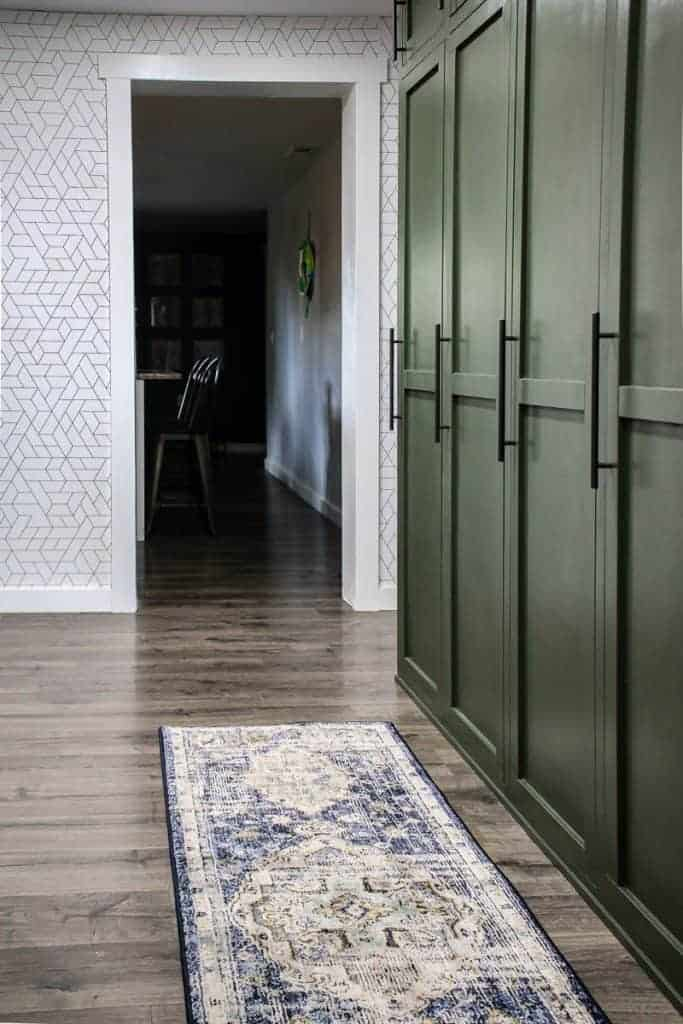 shows a farmhouse green mudroom lockers with blue and white boho runner rug on the gray wood floors in a white geometric wallpaper wall and kitchen in background